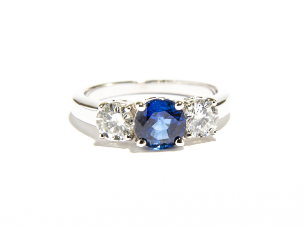 3-Stone Sapphire Center Ring - This 14k white gold ring features 3-stones prong set. The diamonds on either sides total 0.80 carats and the center round sapphire totals 1.0 carat.