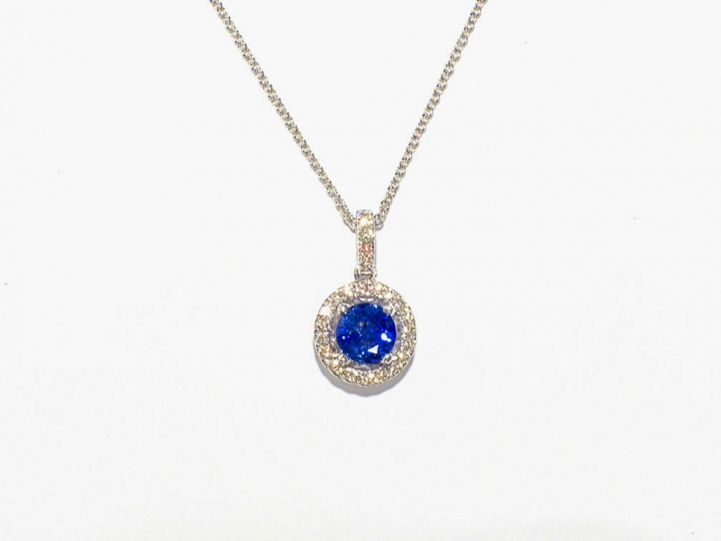 Sapphire Center Diamond Halo Pendant - This 18k white gold pendant was custom made by Travis, our jeweler. The 6mm center sapphire totals 1.18 carats with .28 carats of diamond halo.