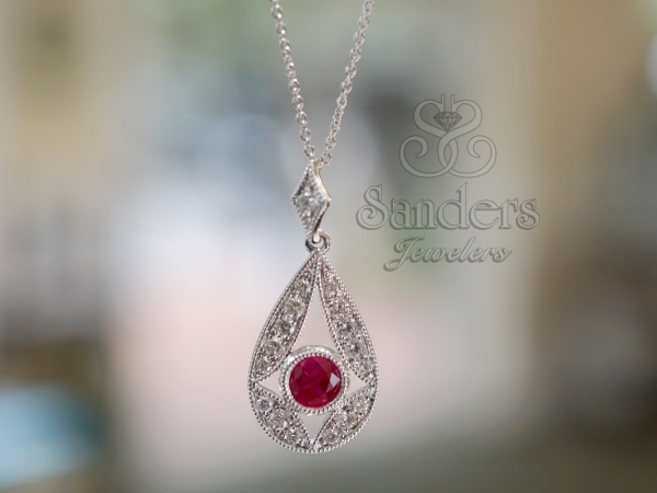 "Ruby and Diamond Pendant - 14K White Gold Ruby and Diamond Pendant. A 0.32 ct Ruby Diamond is set in a bezel surrounded by a sharp geometric pattern of Diamonds. This piece is dynamic with the curvy lines and open work. The ""star"" shape elicits a powerful reaction. This stand out piece is striking when adorned on the neck. (0.20 ctw)"