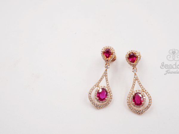 Ruby Earrings - 18K Rose Gold. This elegant design features Rubies set in the complementary Rose Gold metal. The pieces are accented by diamonds and the Rubies themselves each have a Diamond Halo embracing it. (1.17 tw)