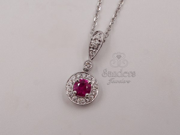 Ruby and Diamond Pendant - 18K White Gold Ruby and Diamond Pendant. A regal Ruby is crowned by a halo of Diamonds, all decorated with millgrain trim. A handful more Diamonds accent the bail. A stunning, classic design. (0.20 ctw)