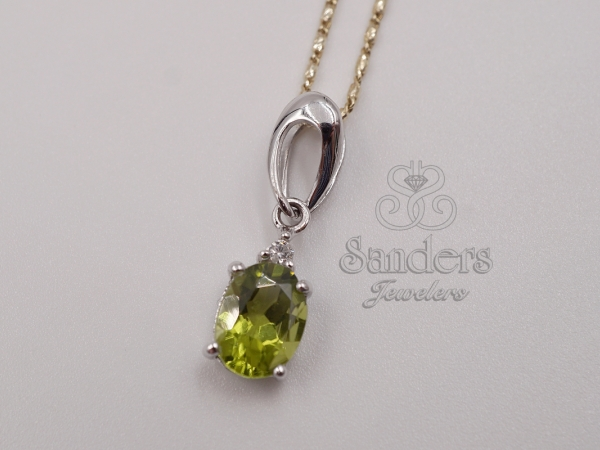 Peridot and Diamond Pendant - 14K White Gold Peridot and Diamond Pendant. A swooping ribbon of white gold gives overall dimension to the piece and acts as the bail. A checkerboard faceted Peridot freely dangles from the bail and is crowned by a Diamond. The pendant is accented by the yellow gold raso chain it is displayed on, though priced separately.(0.03 ctw)
