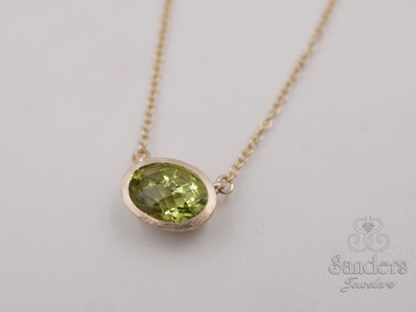 "Peridot Pendant - 18"" 14K Yellow Gold Peridot Pendant. A vibrant Peridot is set east to west in a striking matte finished bezel. The gemstone is fixed to an 18"" chain."