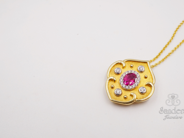 "Ruby Pendant  - 17"" 18K Yellow Gold. A beautifully cut Ruby held in a gold shield pendant. The stone itself is accented by an elegant Diamond halo. With 4 set diamonds in the shield. (0.50 ct)"